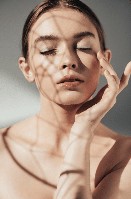 A model with closed eyes brushing her hand over her cheek bone.