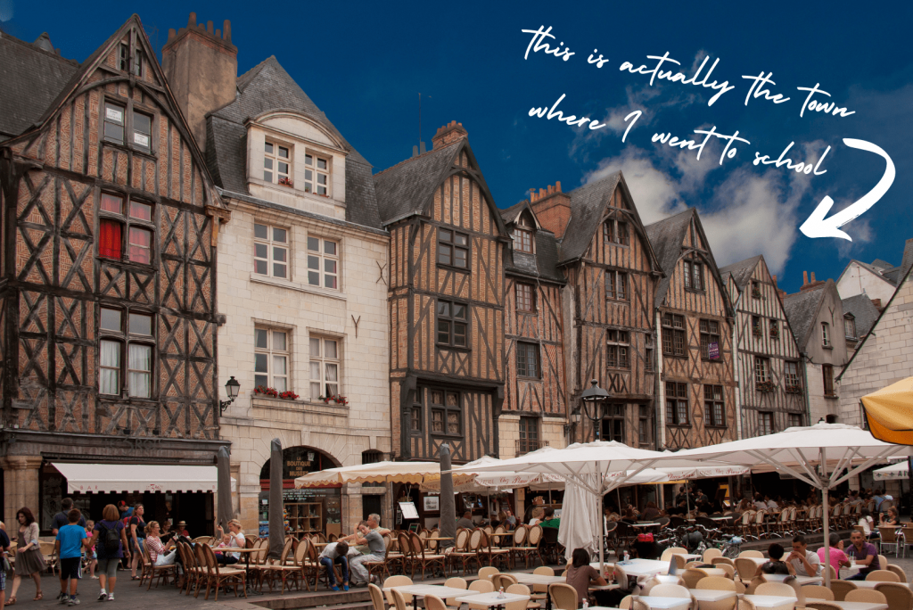 A quaint view of a small French cities main square with coffee shops and people enjoying the atmosphere and smell of fresh coffee.