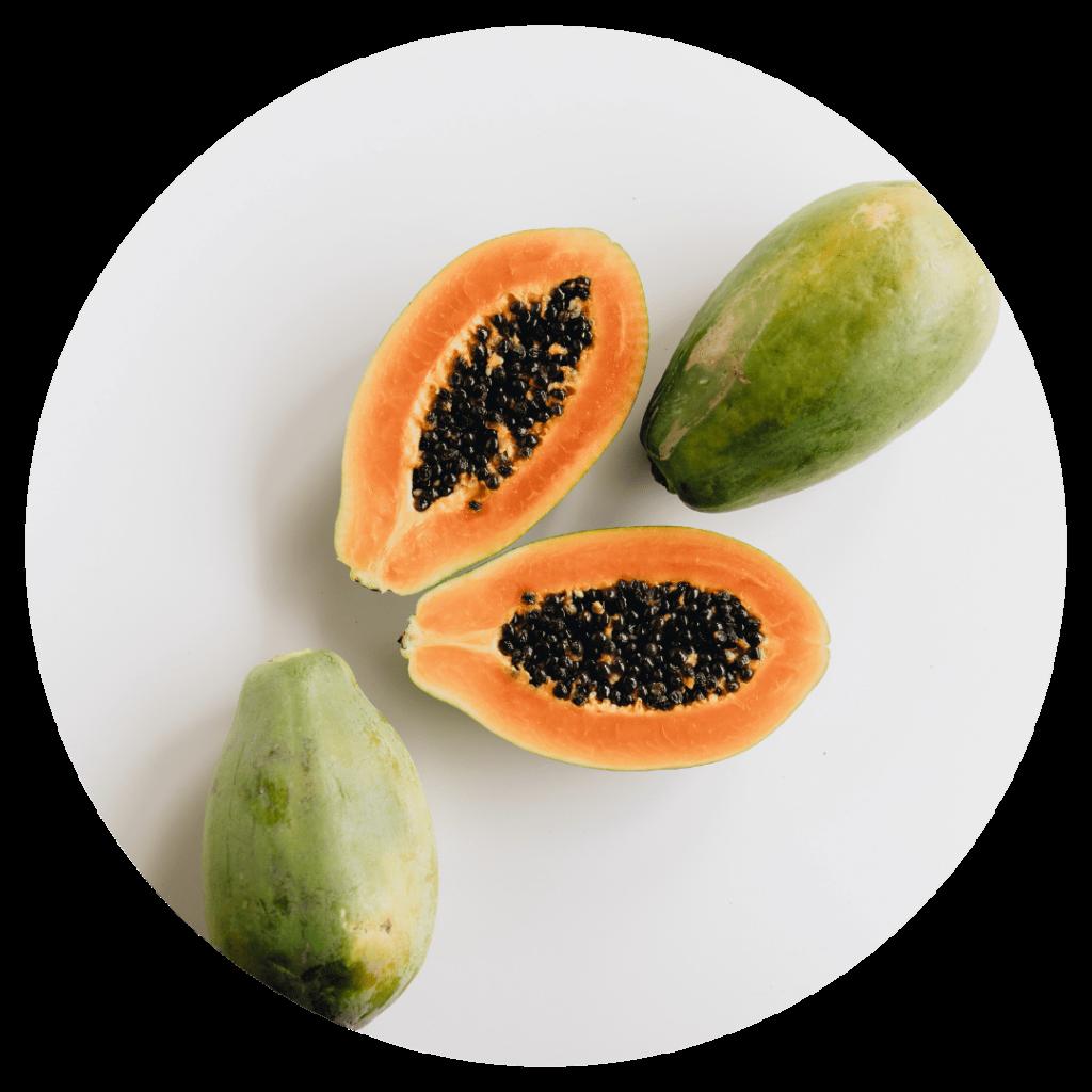 orange centred papaya cut in half. We use papaya seed oil in our brightening facial serum.